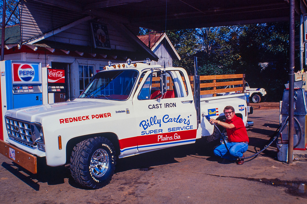 """Billy Carter fuels his new """"Redneck Power"""" pickup truck at his Plains, Georgia gas station. A nodel of the pickup was produced by Revell and sold internationally. William Alton - Billy - Carter (March 29, 1937 – September 25, 1988) was an American farmer, businessman, brewer, and politician, and the younger brother of U.S. President Jimmy Carter. Carter promoted Billy Beer and was a candidate for mayor of Plains, Georgia. Carter was born in Plains, Georgia, to James Earl Carter Sr. and Lillian Gordy Carter. He was named after his paternal grandfather and great-grandfather, William Carter Sr. and William Archibald Carter Jr. respectively. He attended Emory University in Atlanta but did not complete a degree. He served four years in the United States Marine Corps, then returned to Plains to work with his brother in the family business of growing peanuts. In 1955, at the age of 18, he married Sybil Spires (b. 1939), also of Plains. They were the parents of six children: Kim, Jana, William """"Buddy"""" Carter IV, Marle, Mandy, and Earl, who was 12 years old when his father died."""