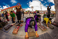Tibetan pilgrims prostrating themselves in Barkhor Square, outside the Jokhang Tmeple (the most sacred temple in Tibet), Lhasa, Tibet, China.