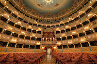 "Teatro La Fenice (""The Phoenix"") in Venice, is one of the most famous and renowned landmarks in the history of Italian theatre as well as those in Europe. La Fenice has faced serious fires twice in its life (1836 and 1996) but risen again as its name (Phoenix) would demand of it. Now restored to its 18th-century glory, the famous opera house boasts a jaw-dropping interior that displays a late-Empire luxury of gilt decorations, plushy extravagance and stucco."
