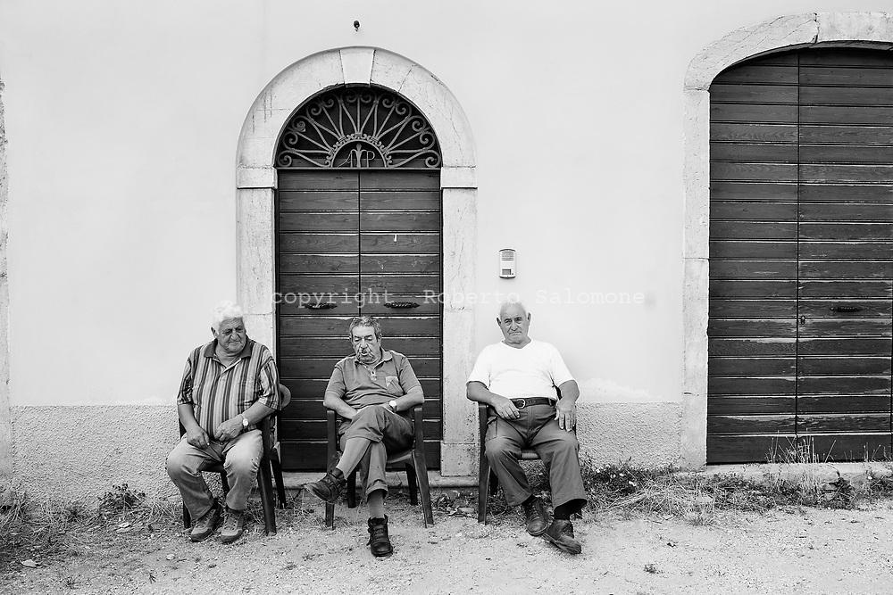 Campi, Italia - Anziani seduti all'esterno di un edificio nel piccolo paese di Campi. Il paese &egrave; disabitato.<br /> Ph. Roberto Salomone