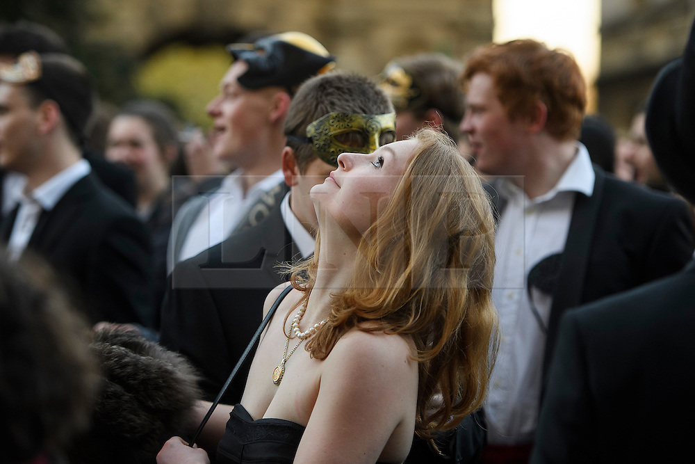 © London News Pictures. 01/05/2016. Oxford, UK.  A young woman watches as a choir sings form the top of Magdalen Tower as part of the May Day day celebrations in the early hours of the morning near Magdalen Bridge in Oxford, Oxfordshire. This year people were again prevented from jumping from the bridge in to the water due to serious injuries sustained at a previous years event . Photo credit: Ben Cawthra/LNP