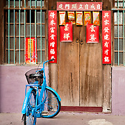 Bicycle and traditional wooden door with spring couplets, Yanshui Village, Tainan County, Taiwan