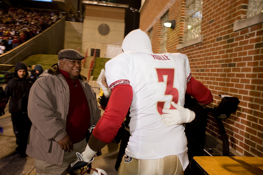College Park, Maryland - Florida State University football player Myron Rolle meets his parents Whitney Rolle, left, and Beverly Rolle (hugging Myron) while entering the playing field at University of Maryland after winning a Rhodes Scholarship earlier that day..Photo by Susana Raab