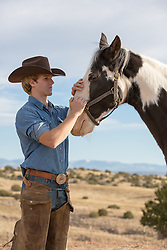 sexy cowboy with a horse outdoors