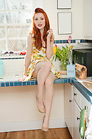 Portrait of a beautiful young woman in short dress sitting on kitchen counter.