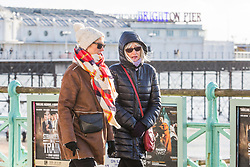 © Licensed to London News Pictures. 07/01/2018. Brighton, UK. Members of the public dress up in scarfs and hats to enjoy some time on the beach and Palace Pier as temperatures drop below 5C on the South Coast. Photo credit: Hugo Michiels/LNP