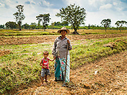 09 MAY 2016 - SANGKHA, SURIN, THAILAND: A woman and her son pose in their rice field in Surin while the woman was hoeing the field and preparing to plant her 2016 rice crop. Normally the fields would have been prepped in April and rice planted in May but farmers are several weeks behind schedule because of the drought in Thailand. Thailand is in the midst of its worst drought in more than 50 years. The government has asked farmers to delay planting their rice until the rains start, which is expected to be in June. The drought is expected to cut Thai rice production and limit exports of Thai rice. The drought, caused by a very strong El Nino weather pattern is cutting production in the world's top three rice exporting countries:  India, Thailand and Vietnam. Rice prices in markets in Thailand and neighboring Cambodia are starting to creep up.     PHOTO BY JACK KURTZ