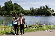 Women feed the pigeons at the Boating Lake in Regent's Park, London