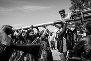 Rebels load a rocket into a Grad launcher in Taminah front line, south east of Misrata. An hour after firing, two salvos of rockets shot by Gadhafi's forces loudly landed next to this position. 14 May 2011.