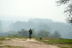 © Licensed to London News Pictures. 02/04/2014. Richmond, UK. A woman walks a dog. Visitors to Richmond Park had low visibility today April 2nd 2013. High levels of air pollution are set to spread across England and are expected  to get worse. Photo credit : Stephen Simpson/LNP