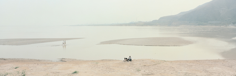 Couple on the banks of the Yellow River. In 1997, the Yellow river symbolised all that was wrong with China's environment: 40% of its waters were severely polluted. The river was so overexploited that it failed to reach the sea for 226 days a year making the prospect of terminal dormancy a realistic possibility. Since then, however, the flow has been unbroken, and in 2010 the ailing river became an award-winning model when the Yellow River Conservancy Commission won the Lee Kwan Yu Water prize in Singapore. But there is still a long way to go before the Yellow river is off life-support. Demand for water in northern China continues to grow faster than efficiency gains. As a result, environmental pressure has shifted from the Yellow river to its tributaries – which are increasingly polluted – and underground aquifers, which are diminishing at an alarming rate. Hejin, Shanxi, China. 2011