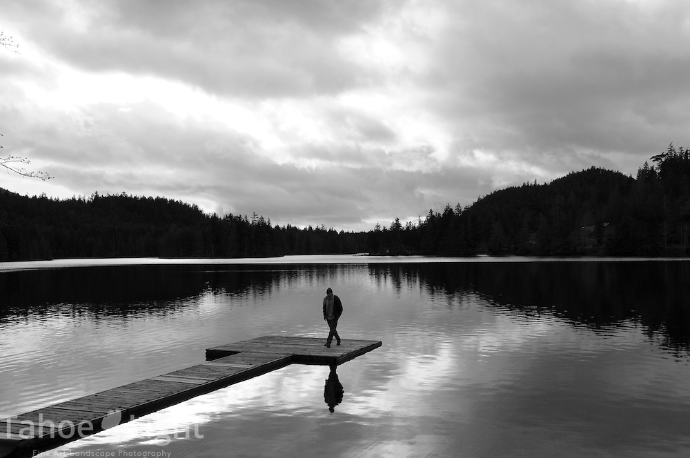 A man walks alone on a dock in a mountain lake in British Columbia