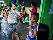 "20 JANUARY 2018 - CAMALIG, ALBAY, PHILIPPINES: A ""taho"" vender (a sort of Filipino custard made with tofu) sells the snack to evacuees at the Barangay Cabangan evacuee shelter in a school in Camalig. There are about 650 people living at the shelter. They won't be allowed to move back to their homes until officials determine that Mayon volcano is safe and not likely to erupt. More than 30,000 people have been evacuated from communities on the near the Mayon volcano in Albay province in the Philippines. Most of the evacuees are staying at school in communities outside of the evacuation zone.  PHOTO BY JACK KURTZ"