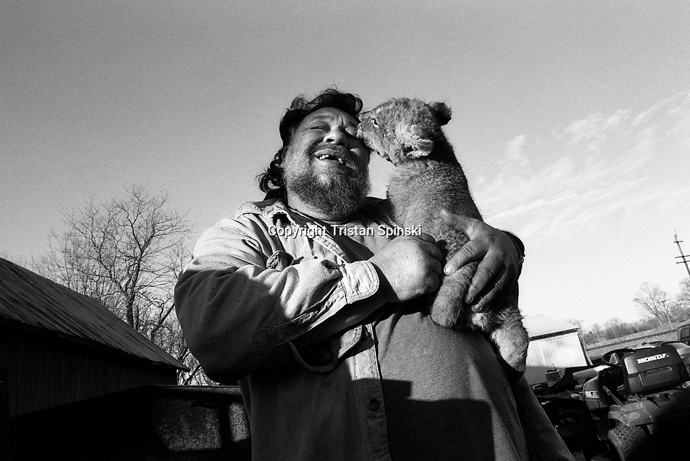 Terry Brumfield, of Piketon, Ohio, hugs his pet African lion cub, Lambert, in his backyard in the fall of 2004.