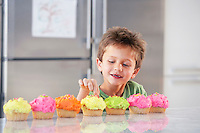 Young boy picking decoration off cupcake in kitchen