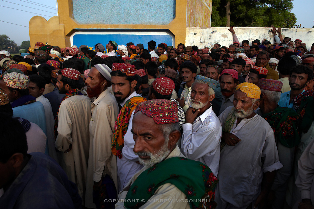 Men wait in line to receive money from the government to help their families to rebuild their lives after the devastating floods which swept through Pakistan in July and August. Each family receieves 10,000 Rupees (approx £75) with the promise of another installment in 6 months time.