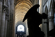 A statue of an angel silhouettes against the stone vaulted ceilings of the Cathédrale Notre Dame de Rouen.