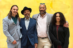 "© Licensed to London News Pictures. 30/05/2019. LONDON, UK. (L to R) Frederik, Benjamin, Sacha and Niamh, Frank Bowling's sons and grandchildren pose in front of ""Mel Edwardes Decides"", 1968, by Frank Bowling at a preview of works by artist Frank Bowling (born in Guyana in 1934).  The retrospective exhibition spans his six-decade career and takes place 31 May to 26 August 2019 at Tate Britain.  Photo credit: Stephen Chung/LNP"