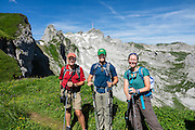 Hikers at Rotsteinpass (2120 m) in Switzerland, Europe. Behind them, a transmission tower caps Säntis (2502 m), the highest mountain in the Alpstein massif of northeastern Switzerland, and highest of the Appenzell Alps. Appenzell Innerrhoden is Switzerland's most traditional and smallest-population canton (second smallest by area). For licensing options, please inquire.