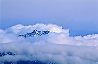 The tip of 14,037 ft. Little Bear Peak of the Sangre De Cristo Mountains.  The peak appears through the winter storm clouds.  Colorado, USA.