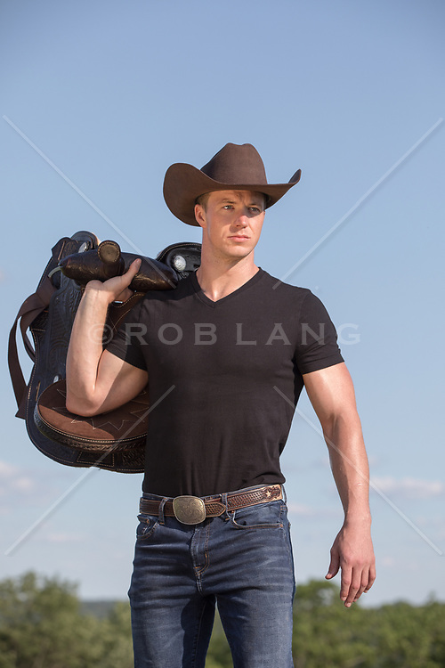 hot cowboy with a saddle over his shoulder on a ranch