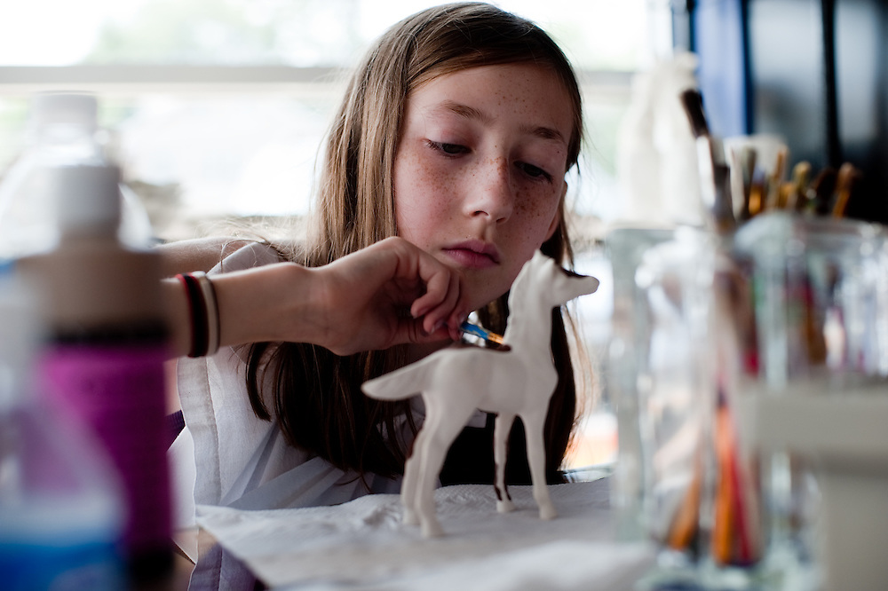 Girl painting a ceramic horse