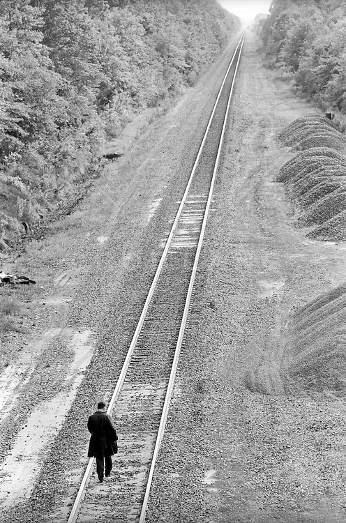 man walking on a deserted railroad track in the country