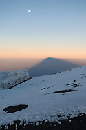 A long shadown is cast by Kilimanjaro as the sun rises over Uhuru Peak.