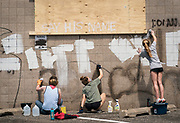 Volunteers remove graffiti from an Aldi grocery store in the Longfellow neighborhood of Minneapolis, Minnesota on Monday, June 1, 2020. The store was damaged extensively during the civil unrest that overwhelmed the Twin Cities in the final days of May following the death of George Floyd at the hands of Minneapolis Police Department officers.