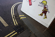 Cartoon graffiti by street artist Nathan Bowen of fireman created outside a London fire station.