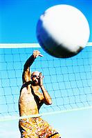 Man spiking a volleyball.
