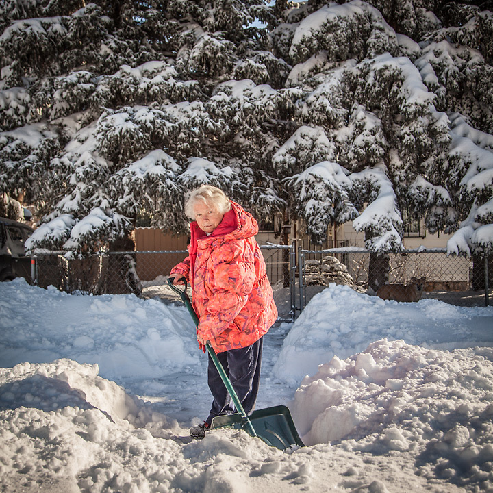 """German imigrant Maitte Pluntke removes snow at the front of her home at 1567 G Street in Anchorage's South Addition neighborhood.  """"We used to have a computer but my husband had a stroke and I got rid of it."""""""