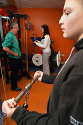 Boy and young woman being watched by instructor using weights at an inclusive fitness gym,