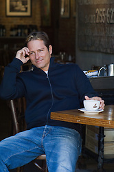 Man sitting at a cafe enjoying a cup of coffee