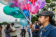 "24 JUNE 2014 - BANGKOK, THAILAND: Members of the ""Monsoon Poets Society"" carry helium balloons in front of the Anantasamakom Throne Hall Tuesday to pay homage to the People's Party, a Siamese (Thai) group of military and civil officers (which became a political party) that staged a bloodless coup against King Prajadhipok (Rama VII) and changed Thailand (then Siam) from an absolute monarchy to a constitutional monarchy on 24 June 1932. Since the coup against the civilian government on 22 May, the ruling junta has not allowed political gatherings. Although police read the poems, they did not arrest any of the poets or make any effort to break up the gathering.     PHOTO BY JACK KURTZ"