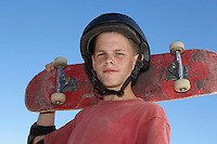 Teenage boy (13-15) holding skateboard outdoors portrait
