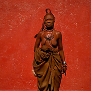 A Himba woman in her traditional attire and her body painted red with a mixture of fat, ash and ochre-colored mud, stands beside a red wall in the town of Opuwo in northwest Namibia. July 10, 2008. Photo by Evelyn Hockstein for The New York Times.
