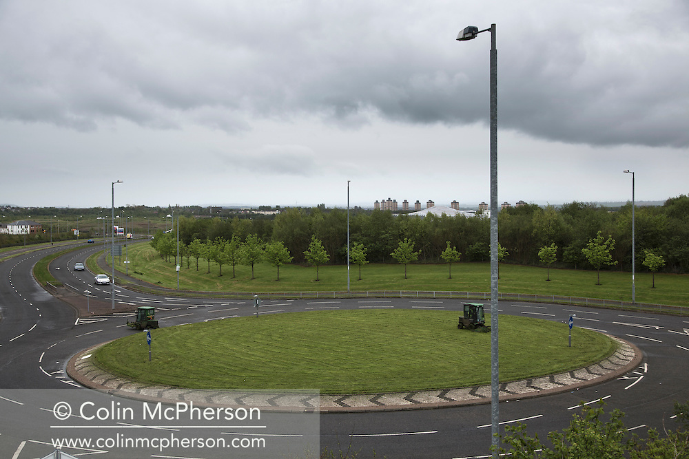 'Untitled, 2014' from the project 'The Fall and Rise of Ravenscraig' by photographer Colin McPherson.<br /> <br /> The photograph shows two grass cutting vehicles working on a roundabout on the so-called 'spine road' built on the site of the former steelworks at Ravenscraig.<br /> <br /> This project, photographed in 2014, looks at the topography of the post-industrial landscape at Ravenscraig, the site until its closure in 1992 of the largest hot strip steel mill in western Europe. In its current state, Ravenscraig is one of the largest derelict sites in Europe measuring over 1,125 acres (4.55 km2) in size, an area equivalent to 700 football pitches or twice the size of Monaco. It is currently being developed with a mix of housing, retail and the home of South Lanarkshire College and the Ravenscraig Regional Sports Facility.