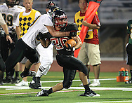 Linn-Mar's Mitch Wantock (20) is pulled down by Kennedy's Joshua Jahlas (30) during the game between Cedar Rapids Kennedy and Linn-Mar at Linn-Mar Stadium in Marion on Friday evening, September 2, 2011. It was 35-7 Linn-Mar at halftime.