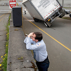 A driver for Conway Transportation Services collects his thoughts after wrecking his semi truck while trying to drive under a railroad bridge over Hewitt Avenue in Everett, Wash.. Though there were no injuries, the Seattle-Chicago mainline railroad had to be closed for inspection.