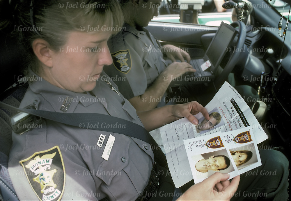 Female Deputy Sheriff, police officer, reviewing outstanding warrants in police car, Putman County Sheriff's Office, FL