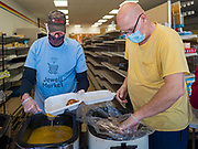 """26 APRIL 2020 - JEWELL, IOWA: KENN OUTZEN and DEAN KOOB, members of the group trying to reopen a grocery store in Jewell, plate up roast pork dinners for grab and go meals during a fund raiser Sunday. Jewell, a small community in central Iowa, became a food desert when the only grocery store in town closed in 2019. It served four communities within a 20 mile radius of Jewell. Some of the town's residents are trying to reopen the store, they are selling shares to form a co-op, and they hold regular fund raisers. Sunday, they served 550 """"grab and go"""" pork roast dinners. They charged a free will donation for the dinners. Despite the state wide restriction on large gatherings because of the COVID-19 pandemic, the event drew hundreds of people, who stayed in their cars while volunteers wearing masks collected money and brought food out to them. Organizers say they've raised about $180,000 of their $225,000 goal and they hope to open the new grocery store before summer.PHOTO BY JACK KURTZ"""