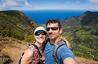 Middle aged couple taking a digital picture of themselves from a viewpoint overlooking Kalalau Valley on the Na Pali Coast, Kauai, Hawaii, USA.