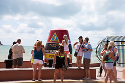 Tourists taking photographs at the Southern Most Point landmark, Key West, Florida, United States of America