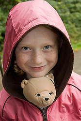 United States, Washington, Bellevue, girl (9 years) with stuffed bear in jacket.  MR