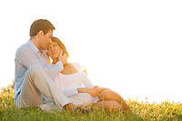 Romantic young couple sitting on grass against clear sky