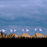 White flags flutter atop beach tents along the shore at Cape May, New Jersey as a storm advances.