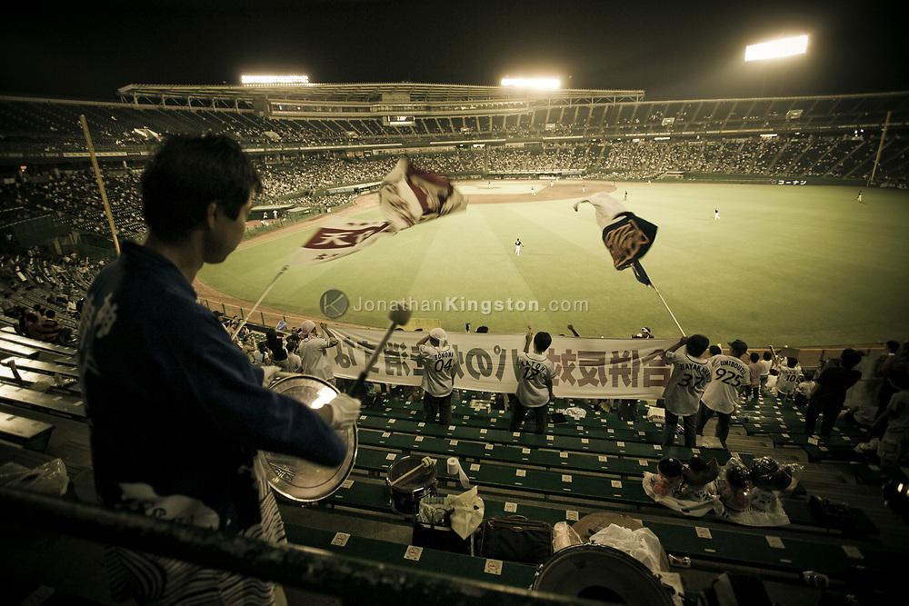 A fan drums a drum during a baseball game at the Orix BlueWave (now the Orix Buffaloes) baseball stadium in Kobe, Japan.  Baseball was introduced to Japan in 1872 and has been a popular sport ever since.