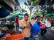 30 JUNE 2016 - BANGKOK, THAILAND:  A man carries a part of a banana tree through Pak Khlong Talat Thursday. Sidewalk vendors around Pak Khlong Talat, Bangkok's famous flower market, face eviction if they reopen on July 1. As a part of the military government sponsored initiative to clean up Bangkok, city officials have been trying to shut down the sidewalk vendors around the flower market. The vendors were supposed to be gone by the end of March, but city officials relented at the last minute with a compromise allowing vendors to stay until June 30. When vendors dismantled their booths after business on June 30, they weren't sure if they will be allowed to reopen July 1. Some vendors have moved to new locations approved by the government but many have not because they can't afford the higher rents in the new locations.    PHOTO BY JACK KURTZ