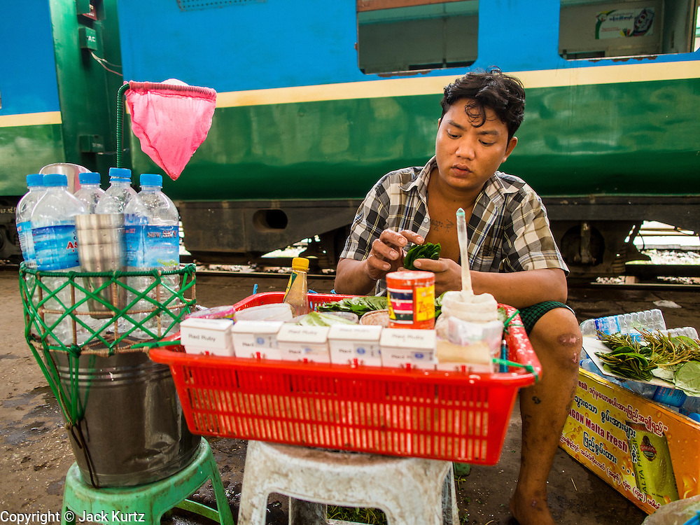 05 JUNE 2014 - YANGON, YANGON REGION, MYANMAR: A vendor prepares betel nut to sell to passengers of the Yangon Circular Train. The Yangon Circular Train is a commuter train that circles Yangon, Myanmar (Rangoon, Burma). The train is 45 kilometers long, makes 38 stops and takes about three hours to make a loop of the city.     PHOTO BY JACK KURTZ